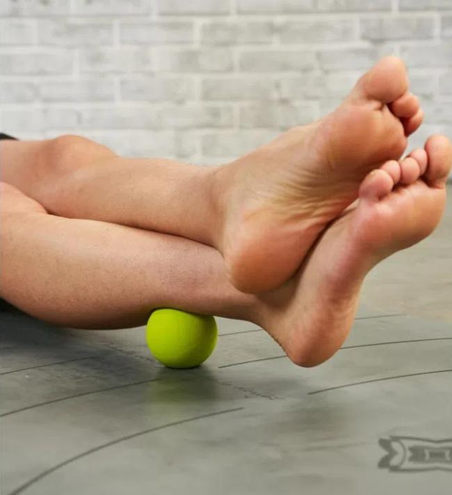 Mostra canelas e pés de uma pessoa apoiadas em uma pequena bola verde