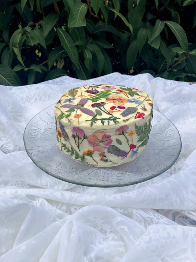 bolo branco coberto por flores prensadas em cima de suporte de vidro colocado sobre tecido branco