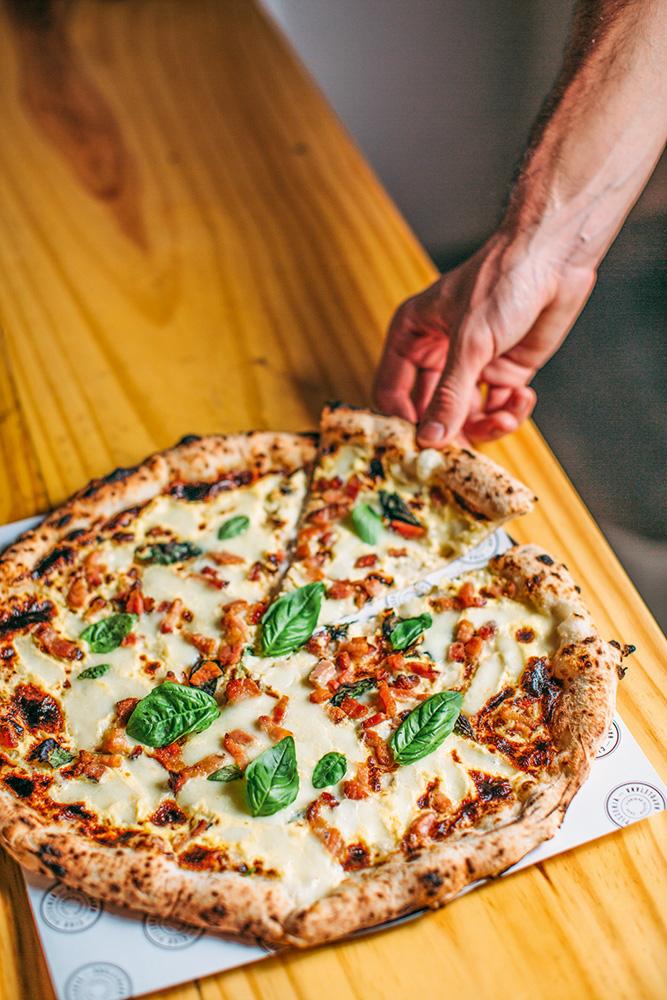 Mão retirando uma fatia da pizza que está sobre balcão de madeira