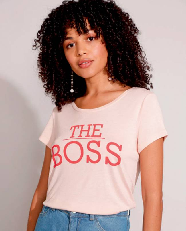 Mulher negra com cabelos cacheados veste blusa rosa com o escrito