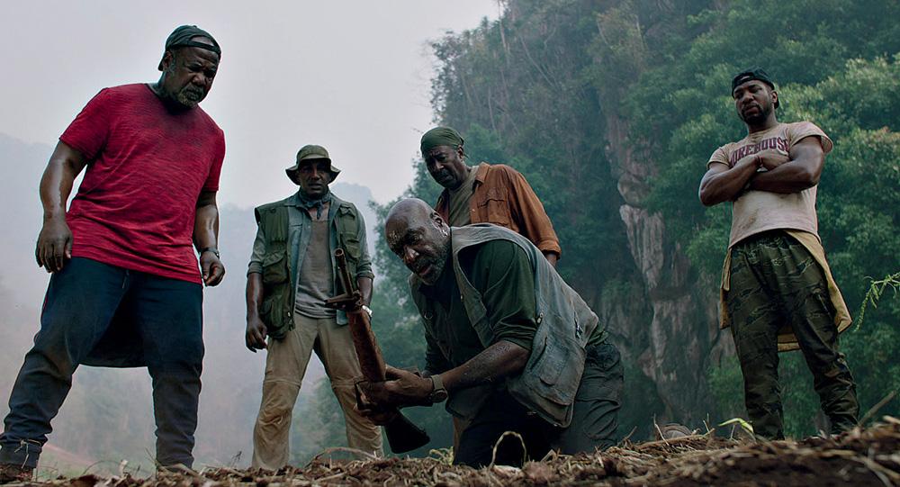 Cinco homens negros olham para um objeto segurado por um deles perto do chão de terra