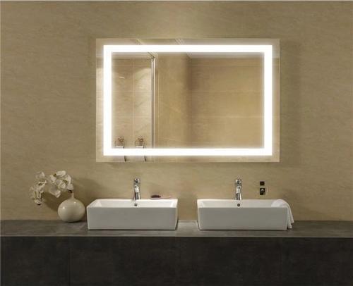 Banheiro em frente a um espelho retangular com luz de led com duas pias embaixo