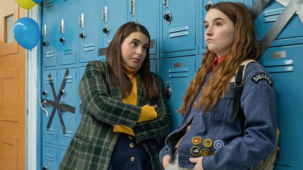 Duas meninas conversam apoiadas em armários escolares azuis