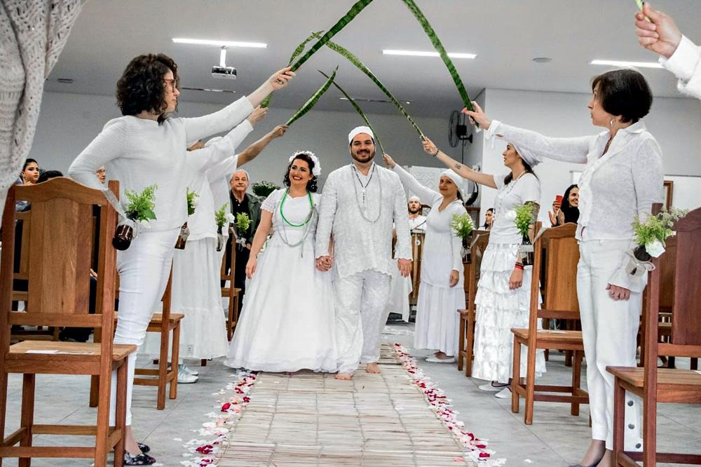 Daniel e Tatiana entram em sua cerimônia umbandista de casamento sendo recebidos pelos convidados segurando folhas de espada-de-são-jorge