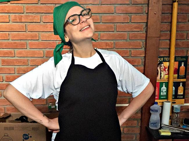 mulher com mãos na cintura sorrindo vestida com avental e lenço na cabeça