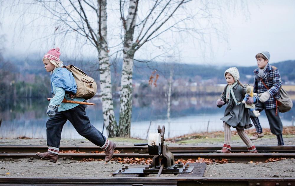 As três crianças do filme, com roupas de frio, corrento sobre um trilho de trem