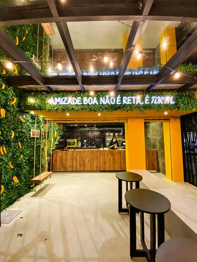 Salão da doceria Nanica com parede de plantas ao lado esquerdo, balcão ao fundo e banquinhos de madeira a direita