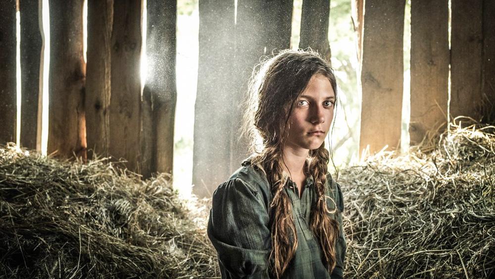 Zuzanna Surowy, em imagem do filme, encara a câmera com um fundo onde há feno e paredes de madeira
