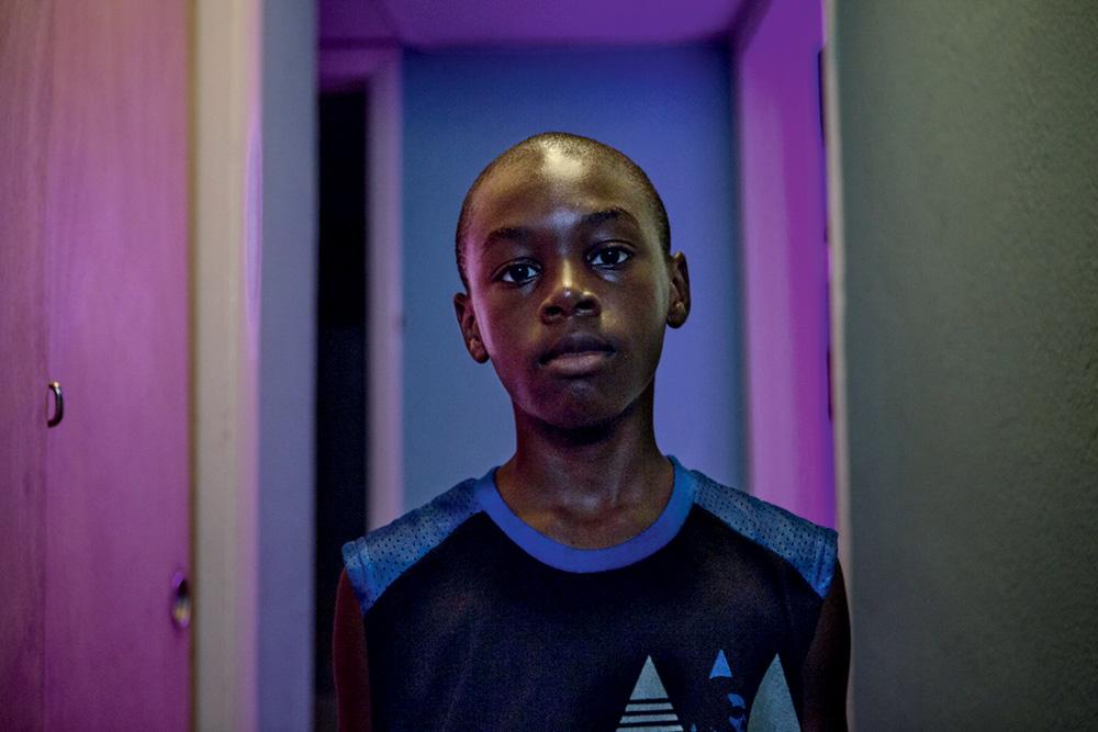 Menino negro e suado encara a câmera com feição séria