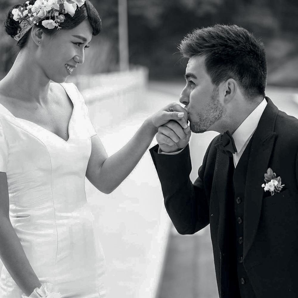 Casal vestido de noivo e noiva, de lado para a foto, com Lucas beijando a mão de Sisi