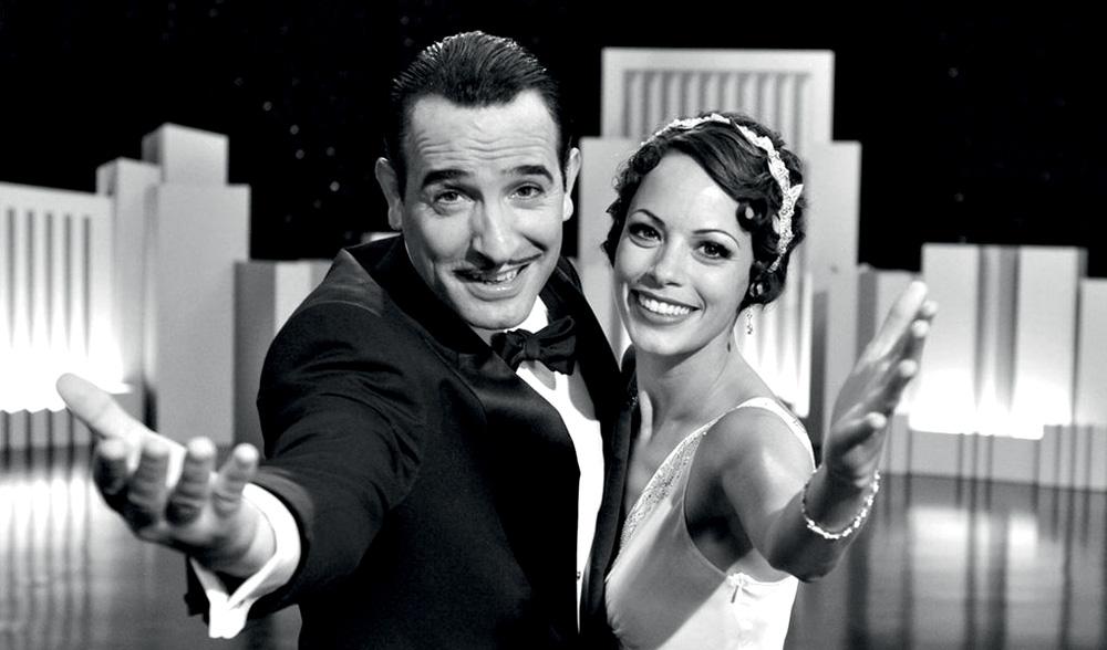 Em preto e branco, um homem e uma mulher, lado a lado, esticam o braço para câmera sorrindo