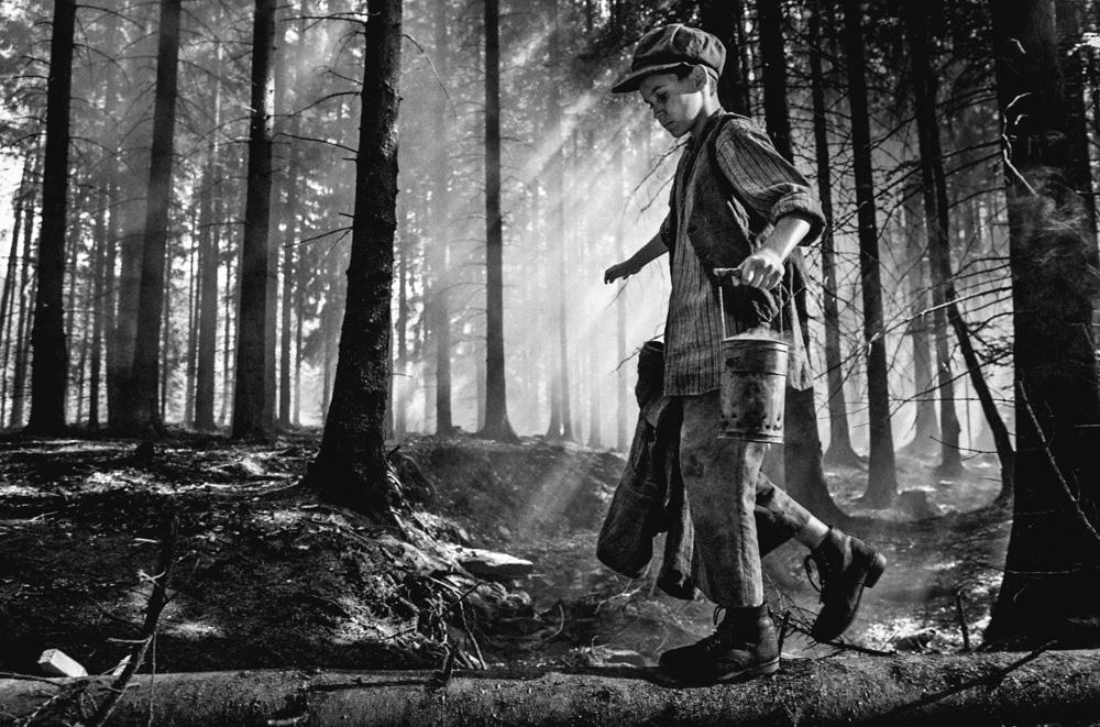 Petr Kotlár, em uma imagem preta e branca, anda com roupas tradicionais do leste europeu da época da ll Guerra. Ele está em meio a uma floresta.