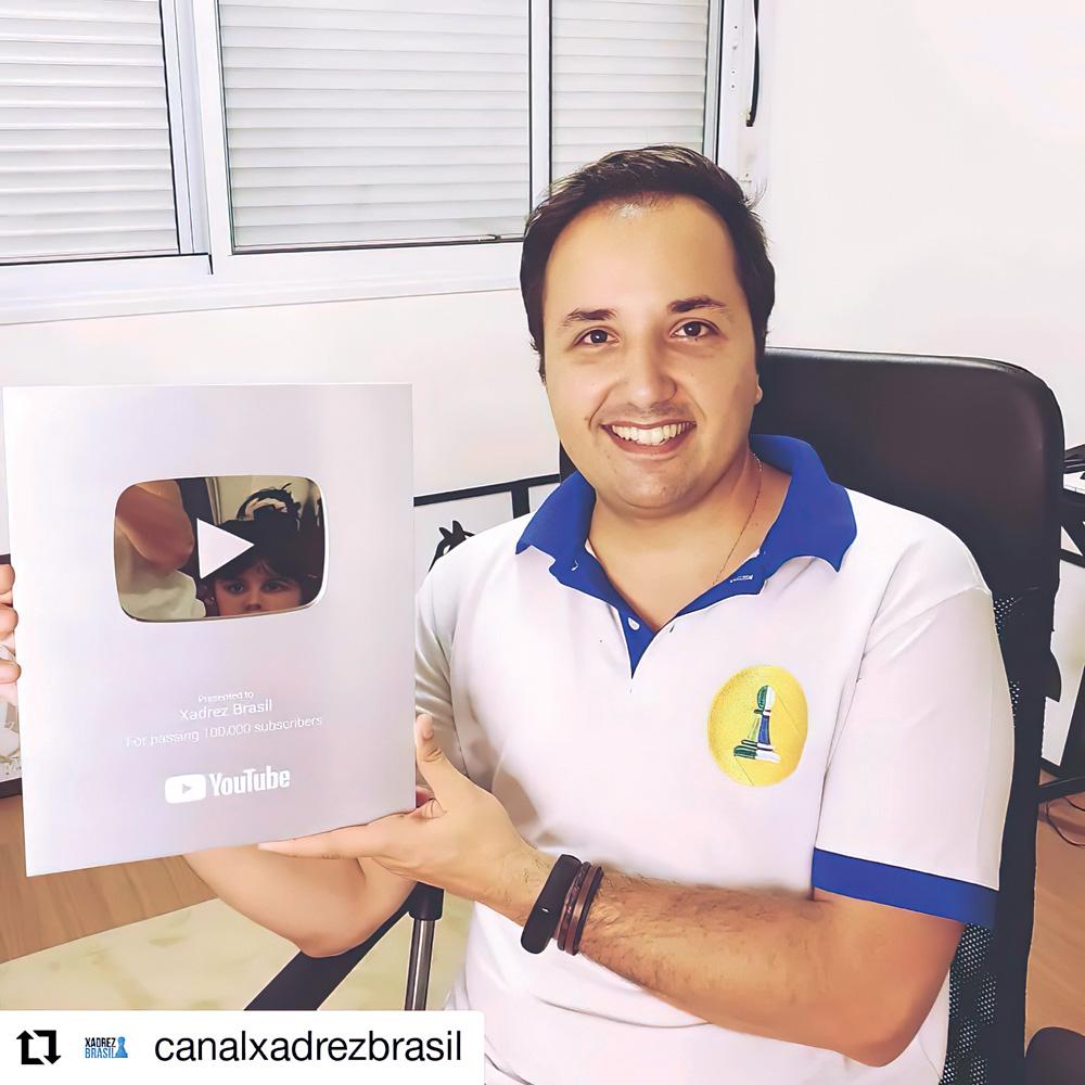Rafael posando para a foto segurando sua placa comemorativa de 100 mil inscritos no youtube