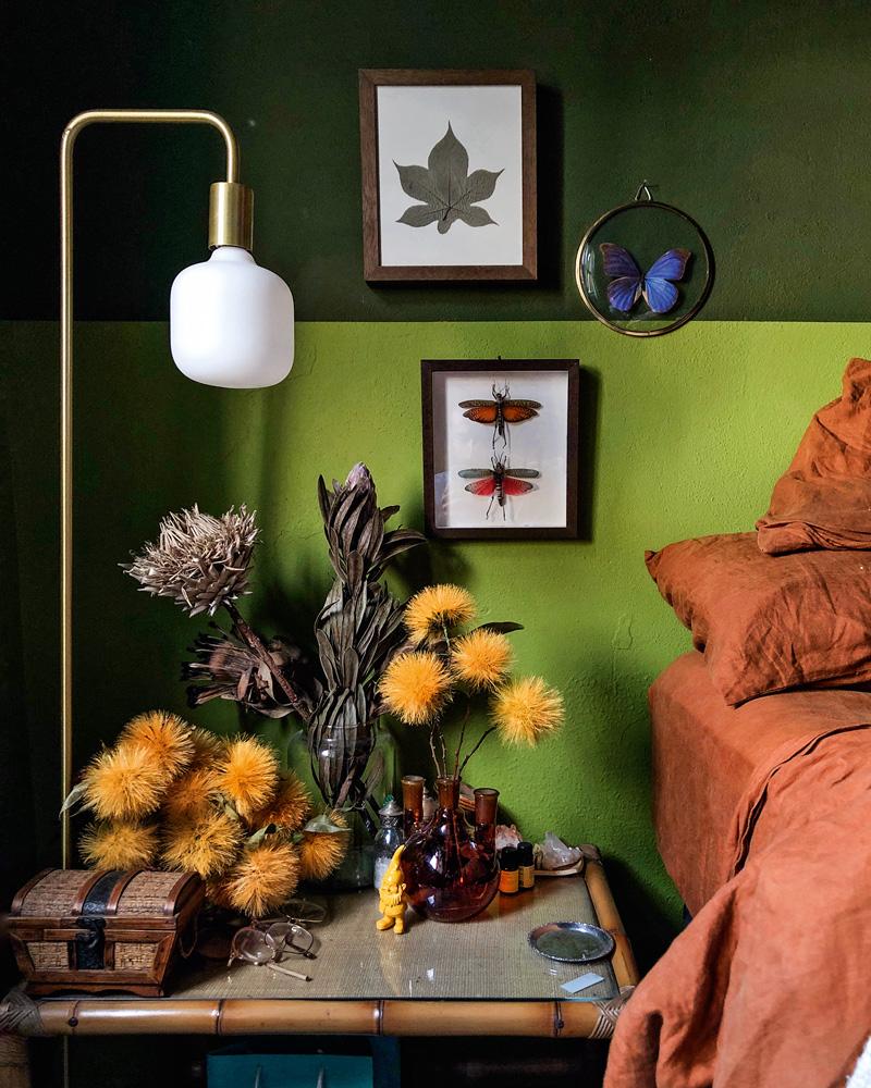 Parede pintada com dois tons de verde, com o mais escuto na parte superior. Também há quadros