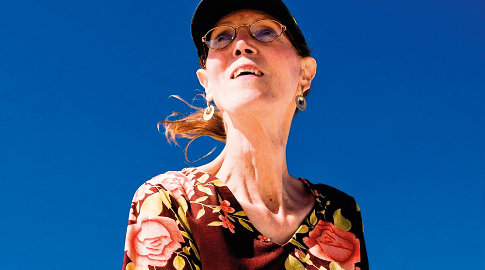 Foto mostra mulher olhando para cima com cabelo preso ventando. Céu azul de fundo