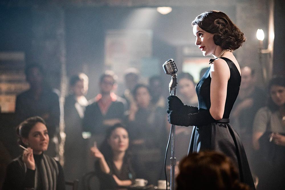 Uma mulher, no cenário e com roupas dos anos 1950, segura um microfone em frente a uma plateia