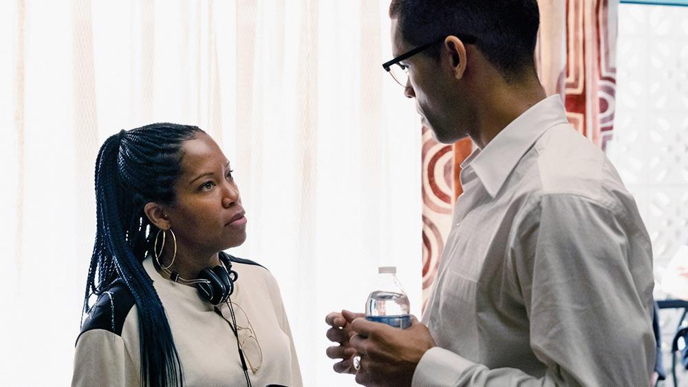 Uma mulher negra de dreads olha séria para um homem de camiseta social na sua frente