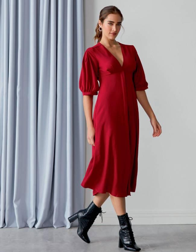 Mulher caminha com vestido vermelho olhando para câmera