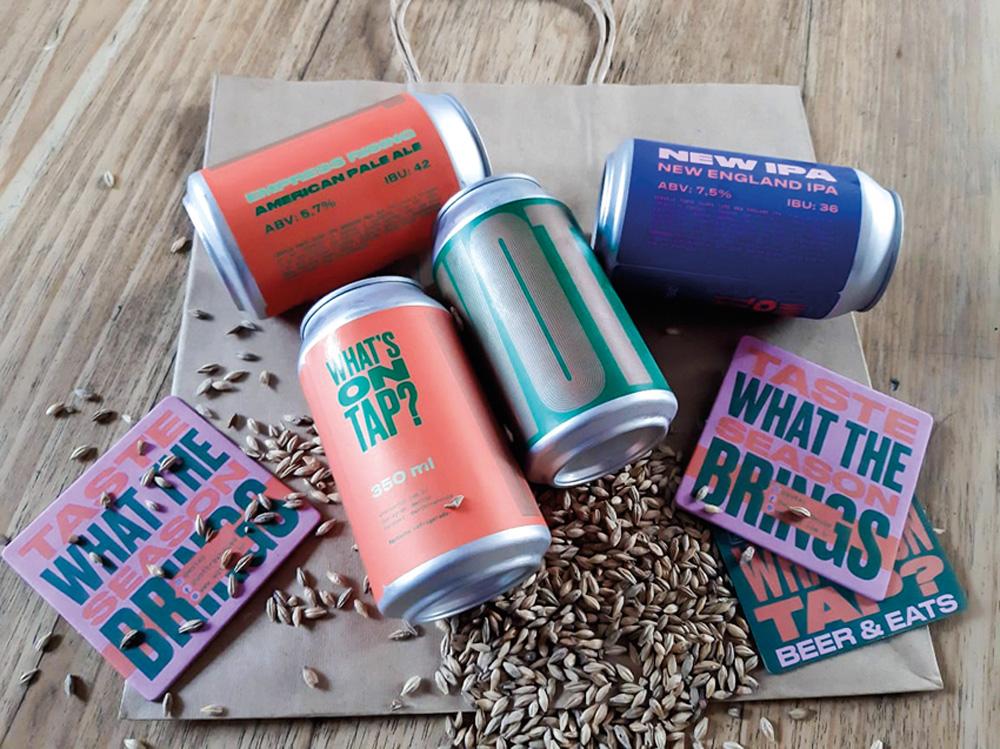 Quatro latas de cerveja nas cores laranja, azul e verde deitadas em uma superfície de madeira com grãos.
