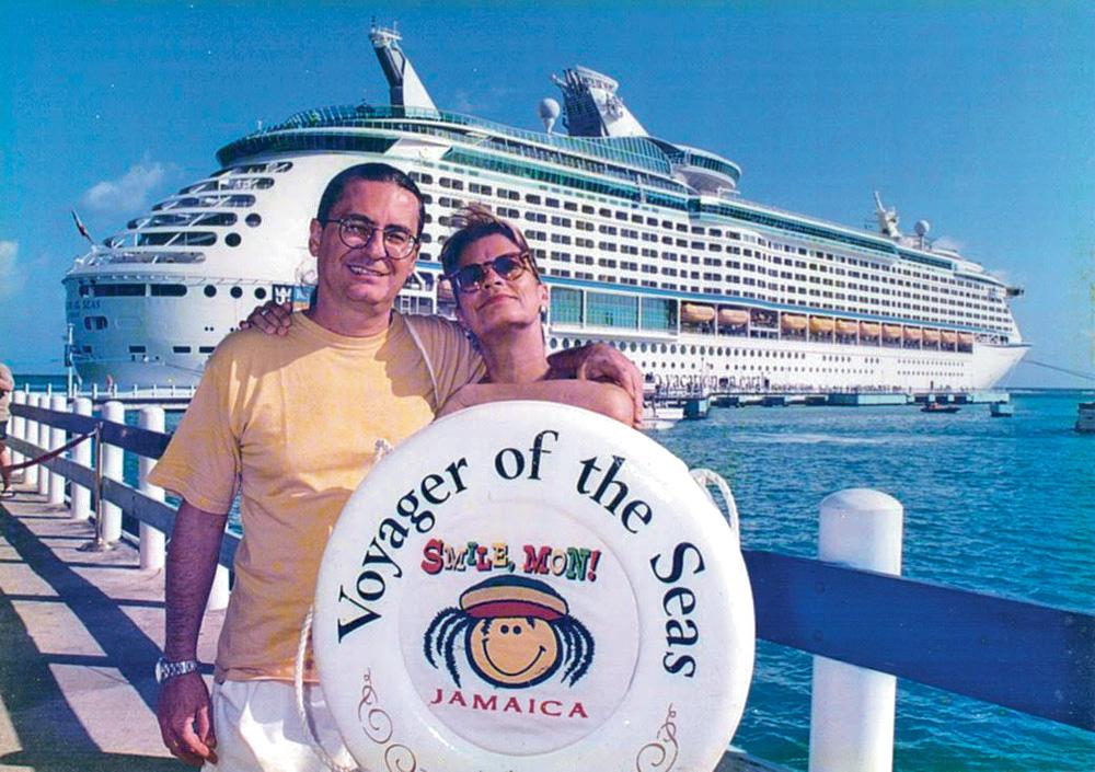 Bicôa e Léo posando para foto segurando boia de cruzeiro, com o navio ao fundo