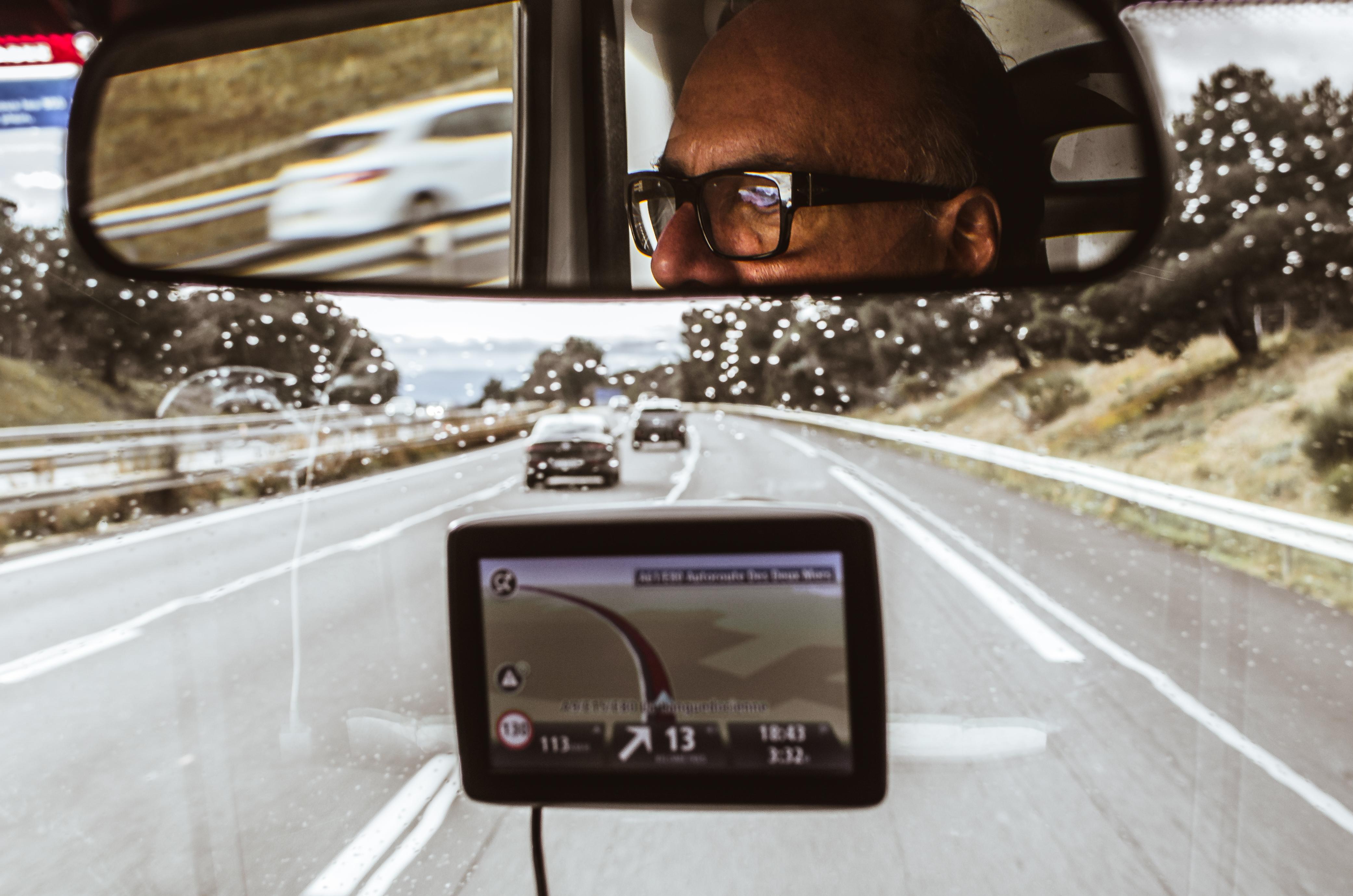 Rosto de Arnaldo Danemberg com óculos de grau aparecem no retrovisor de um caminhão. Em frente, a foto exibe a estrada e um GPS.