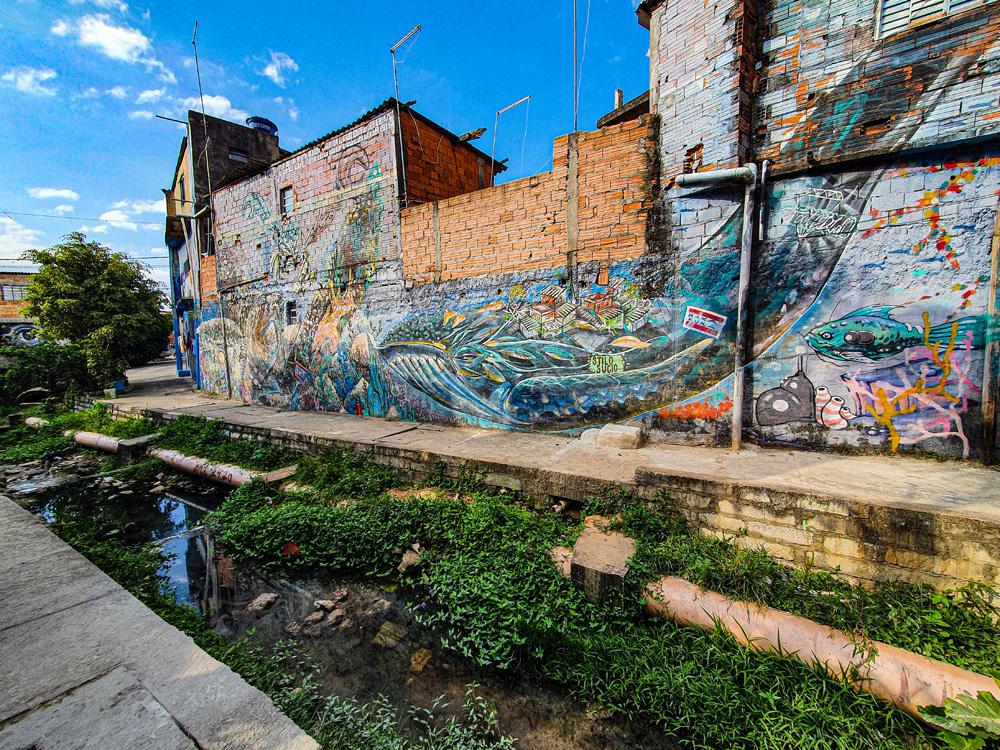 Lado de uma casa pintado com um grande grafite de uma baleia bem colorida