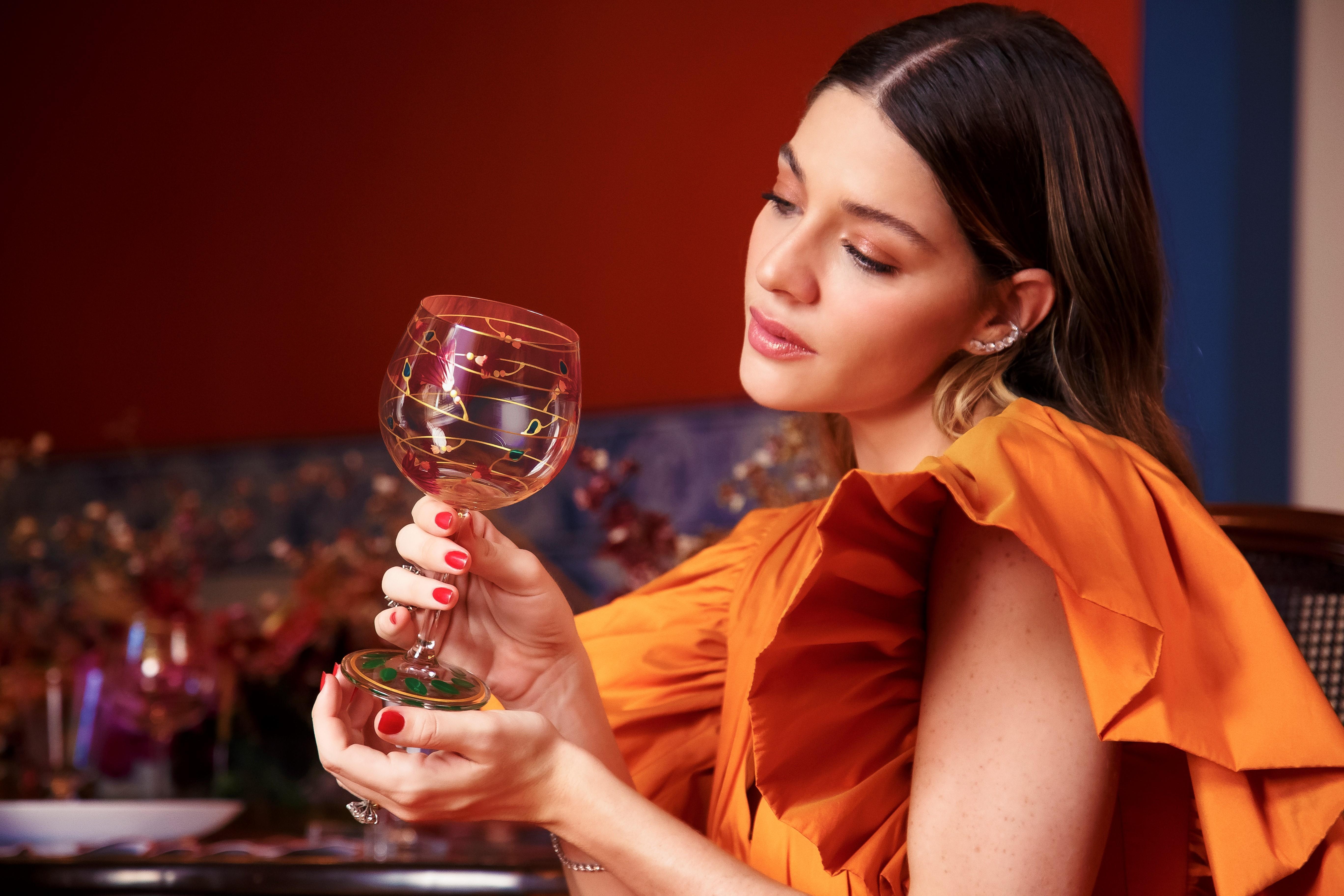 Atriz Luma Costa posa com vestido laranja e segura uma taça de vidro decorada com desenhos coloridos.