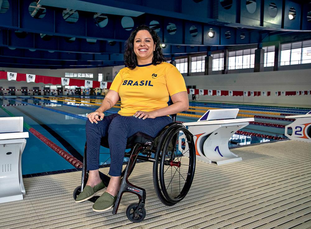 A fotografia mostra Edênia, de cadeira de rodas, em frente à uma piscina de natação. Ela está com a camisa amarela escrito Brasil e sorrindo para a foto.