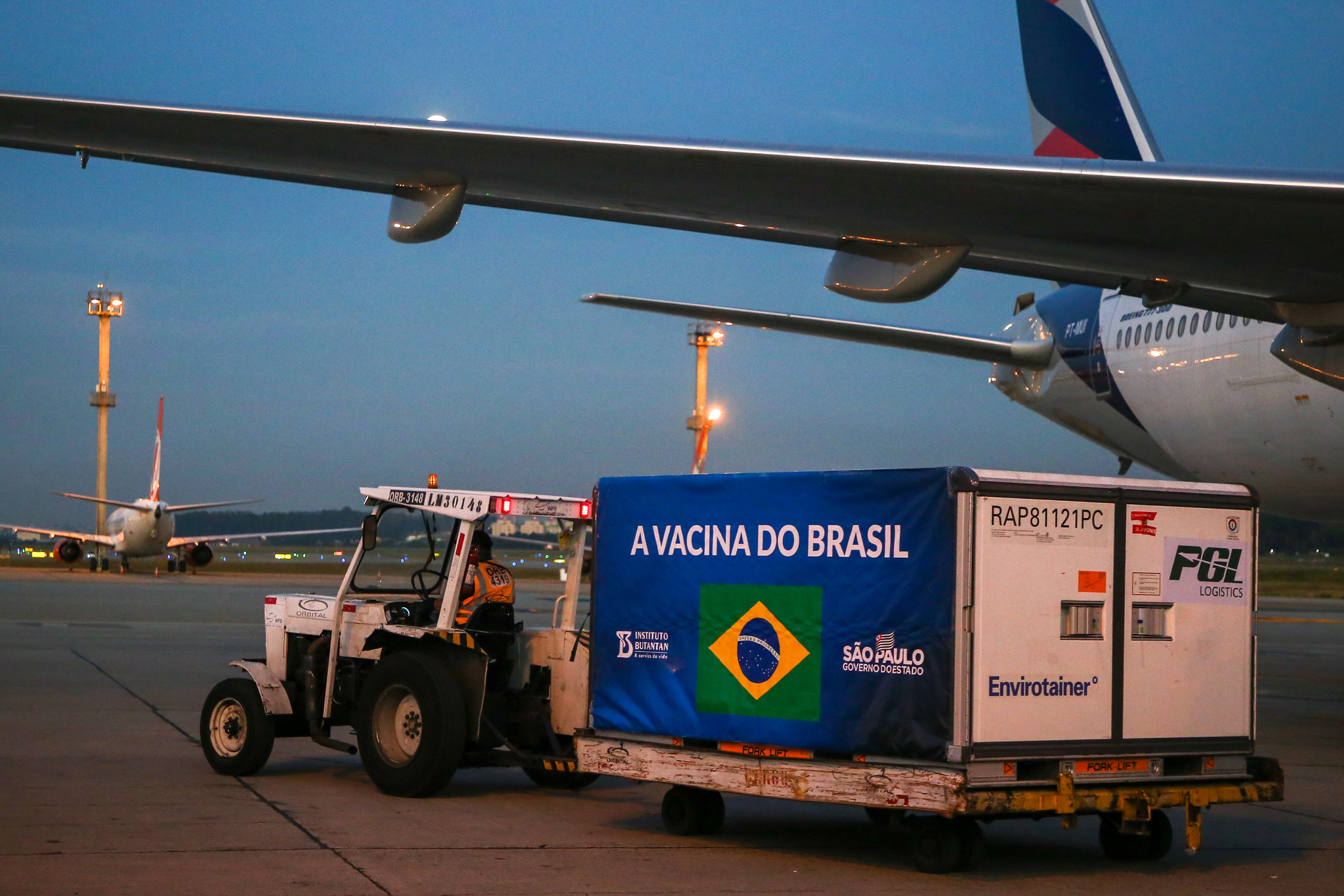 Imagem mostra trator transportando contêiner estampado com logo do Brasil, em que se lê