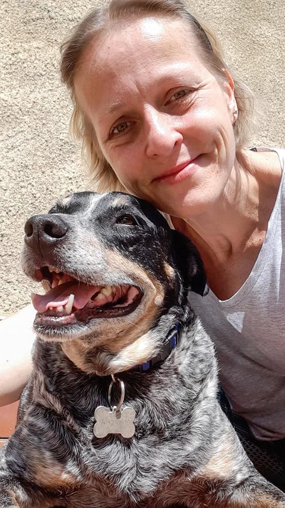 Uma mulher loira abraça um cachorro grisalho que está com a boca aberta
