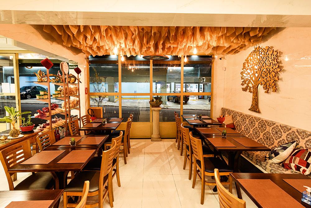Salão pequeno do restaurante Shahiya com mesas espalhadas dos lados direito e esquerdo.