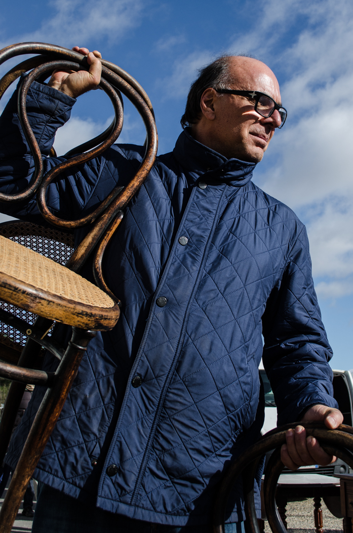 Arnaldo Danemberg segura duas cadeiras, uma erguida com o braço. veste jaqueta azul-escuro.
