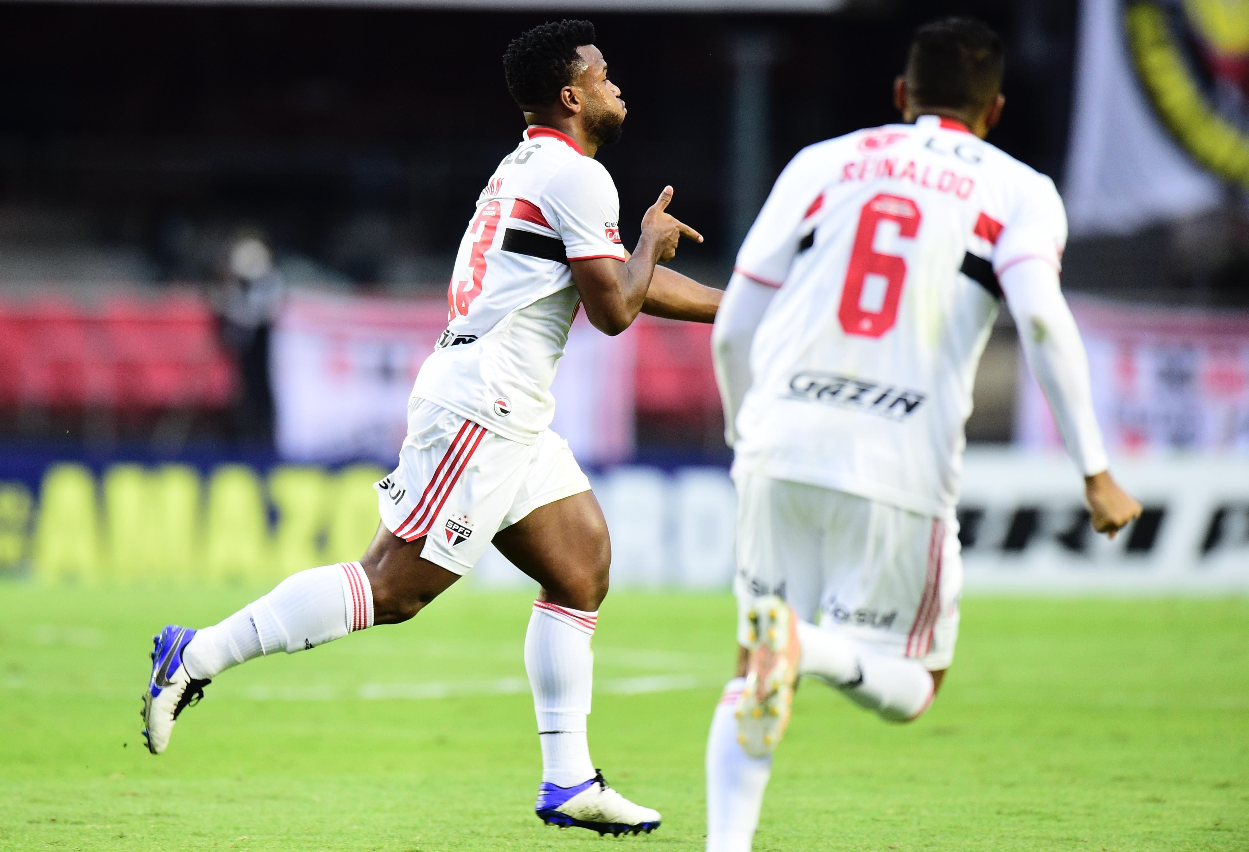 A imagem mostra Luan seguido de Reinaldo comemorando gol no gramado do Morumbi.