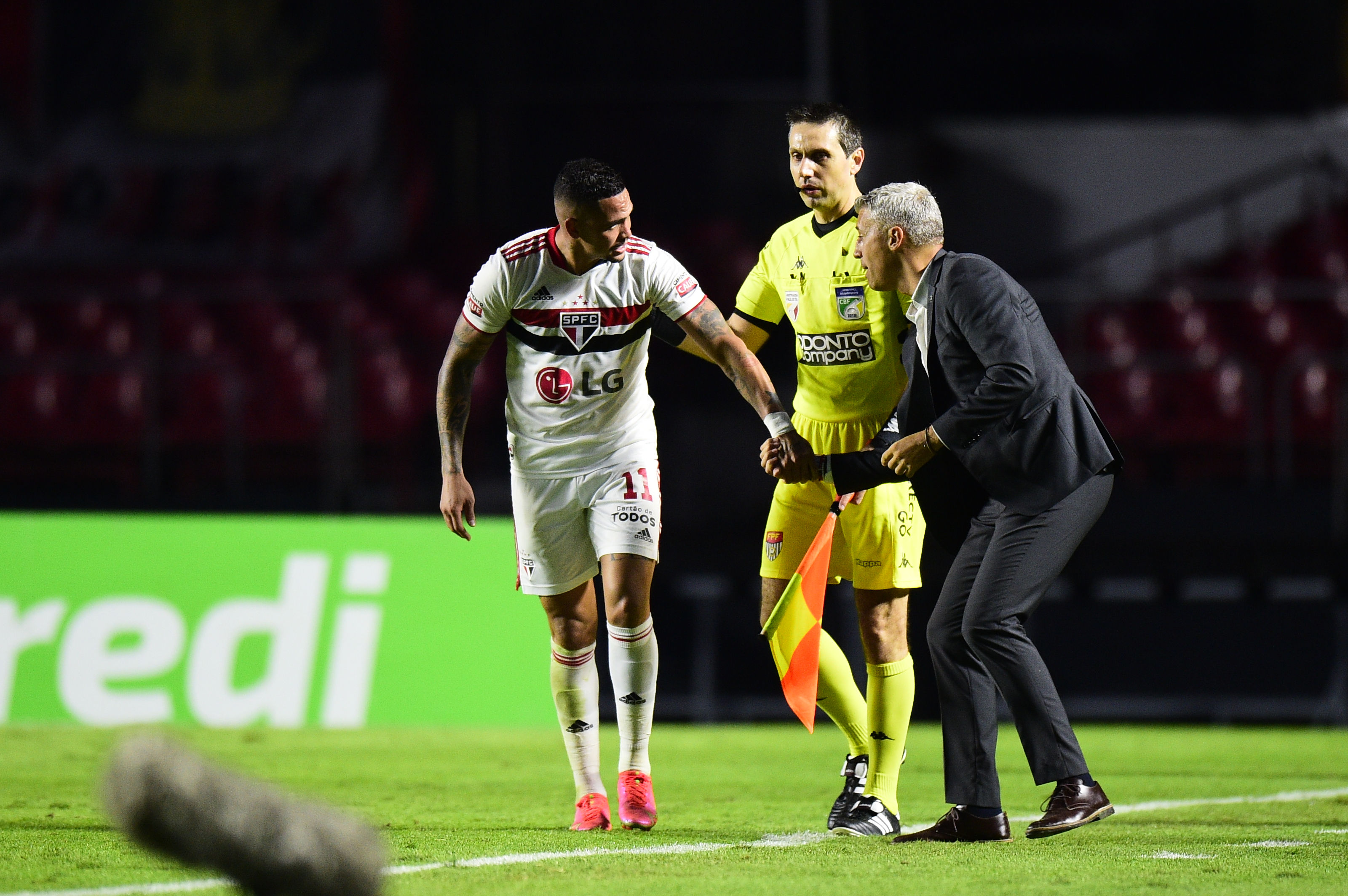 A imagem mostra Crespo segurando nas mãos de Luciano enquanto fala algo para o atleta.