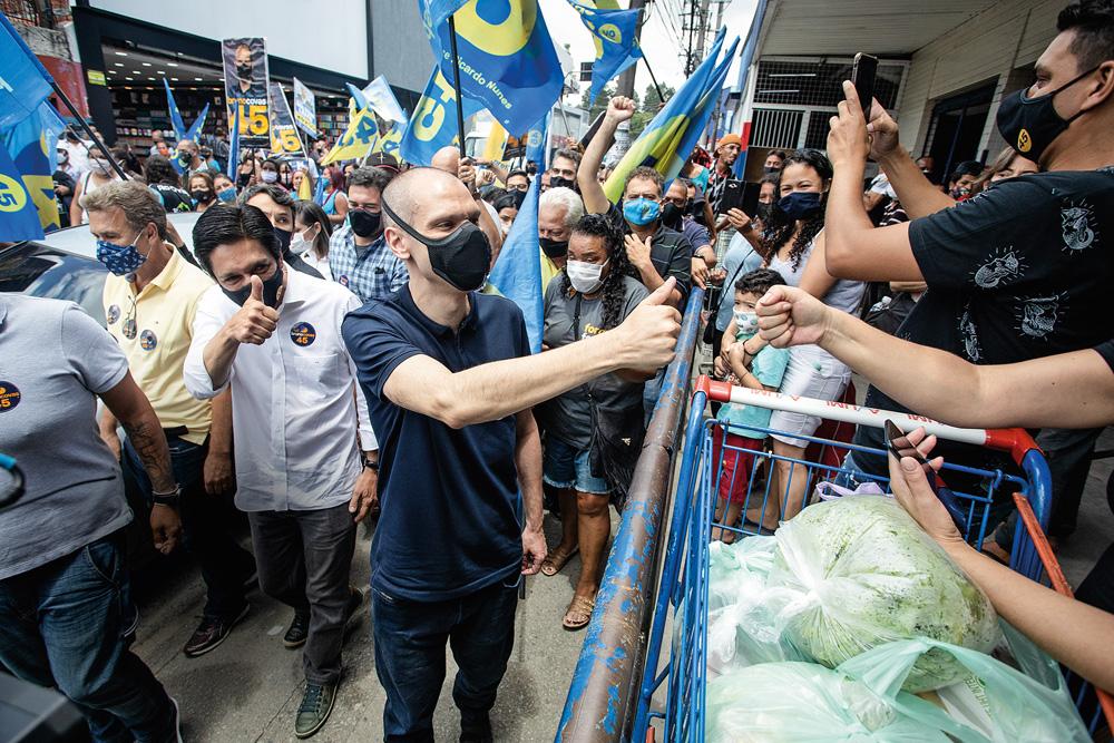 A imagem mostra Covas e Nunes em campanha, nas ruas, cercado de apoiadores e bandeiras com nome e número do ´partido. Eles estão de máscara.