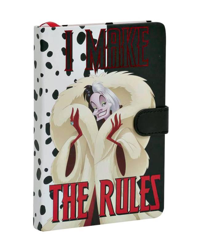 Caderno de anotações. Na estampa, desenho da personagem Cruella. Fundo é preto e branco com patinhas de cachorro. Há a frase