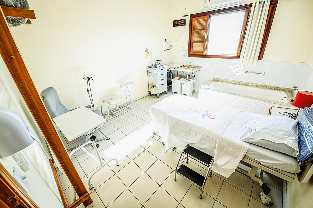 Sala de parto na Casa Angela. Maca, banco, pia e aparelhos médicos. Foto tem luz da claridade mostrada pela janela