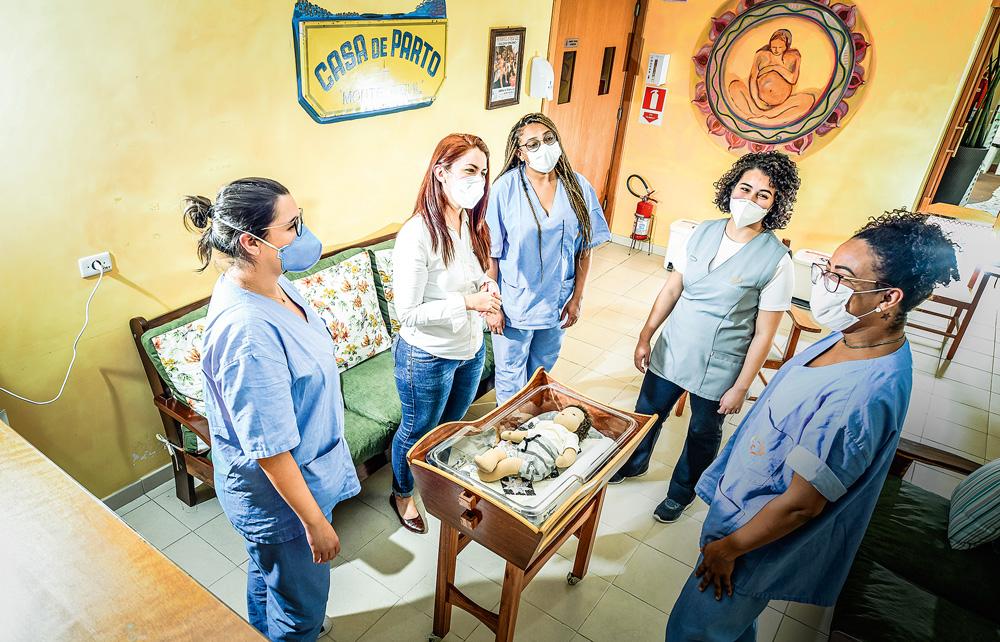 Enfermeiras e técnicas de enfermagem, uniformizadas, conversam entre si em uma roda. Um berço com um bebê de boneca está no meio da roda