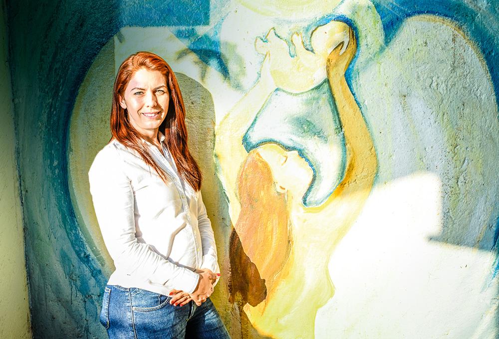 Mulher ruiva, de camisa social, posa em frente a uma pintura de mãe e bebê na parede