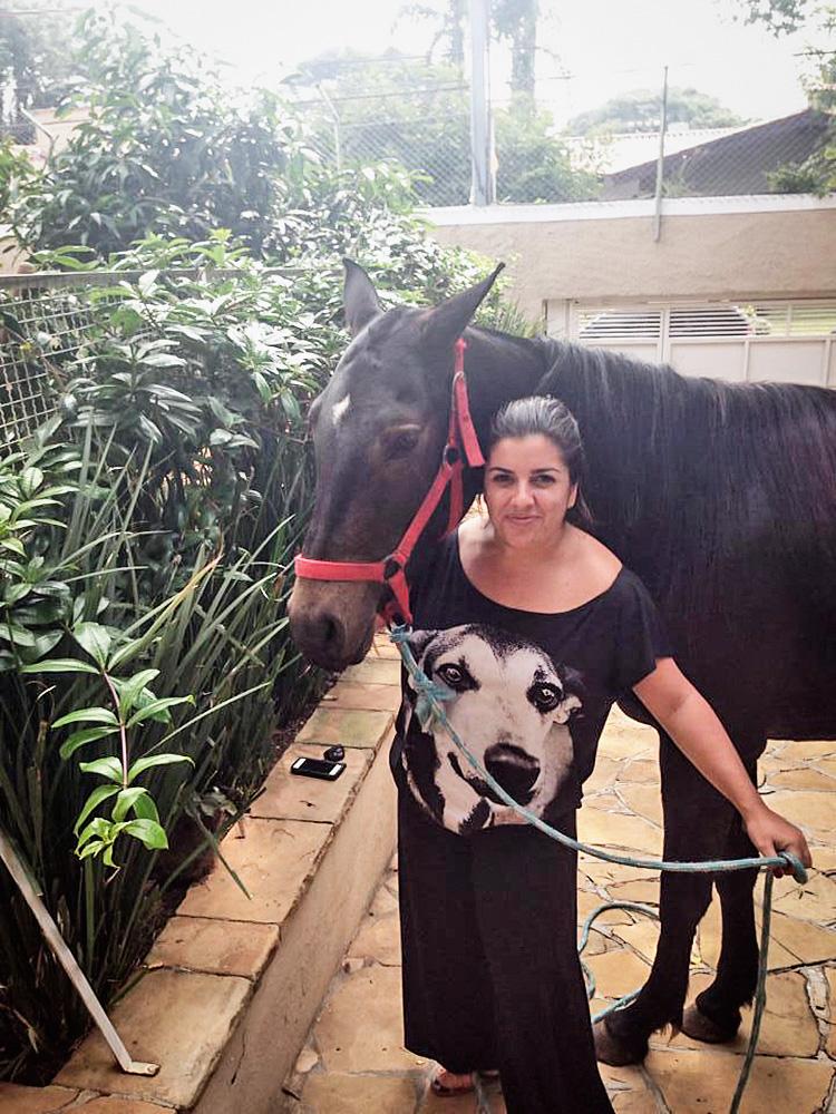Uma mulher posa com um cavalo ao lado de uma grama vertical