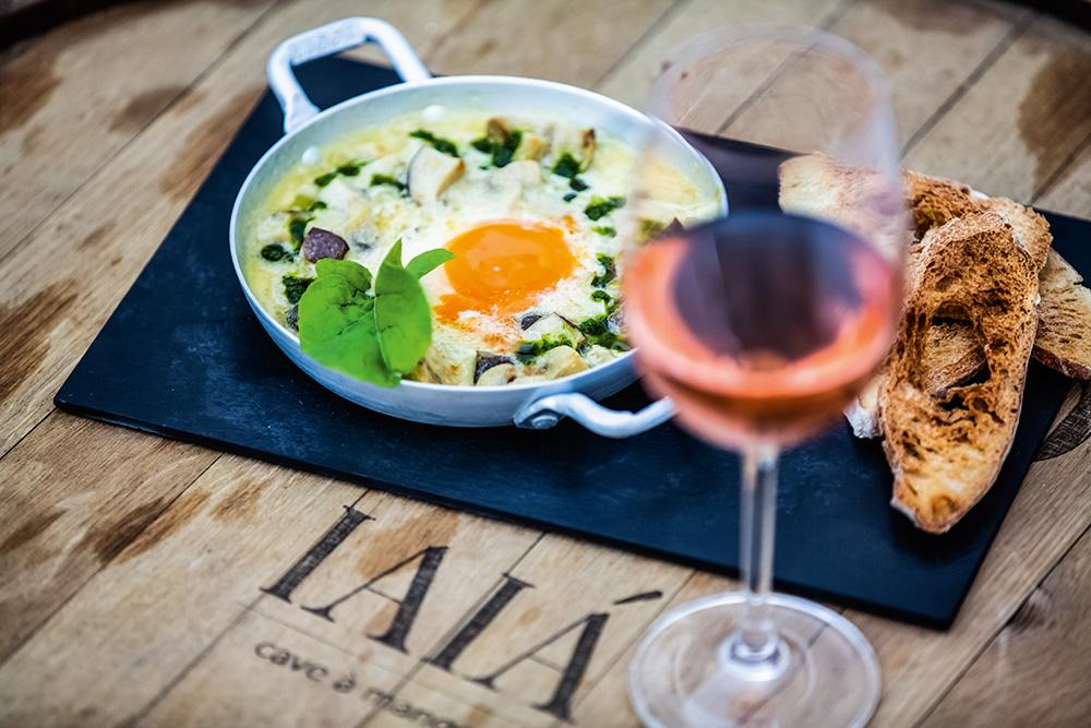 Imagem focada em panelinha de metal na porção superior esquerdo com creme de cogumelos com gema de ovo ao centro. À direita do prato, desfocada, aparece uma taça de vinho rosé com fatias de pão ao lado.