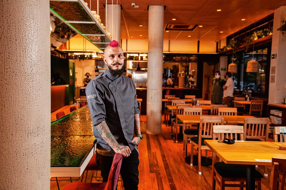 Chef Rafael Lorenti à esquerda, de dólmã e cabelo rosa, no salão do restaurante Basilicata Trattoria. Mesas à direita.