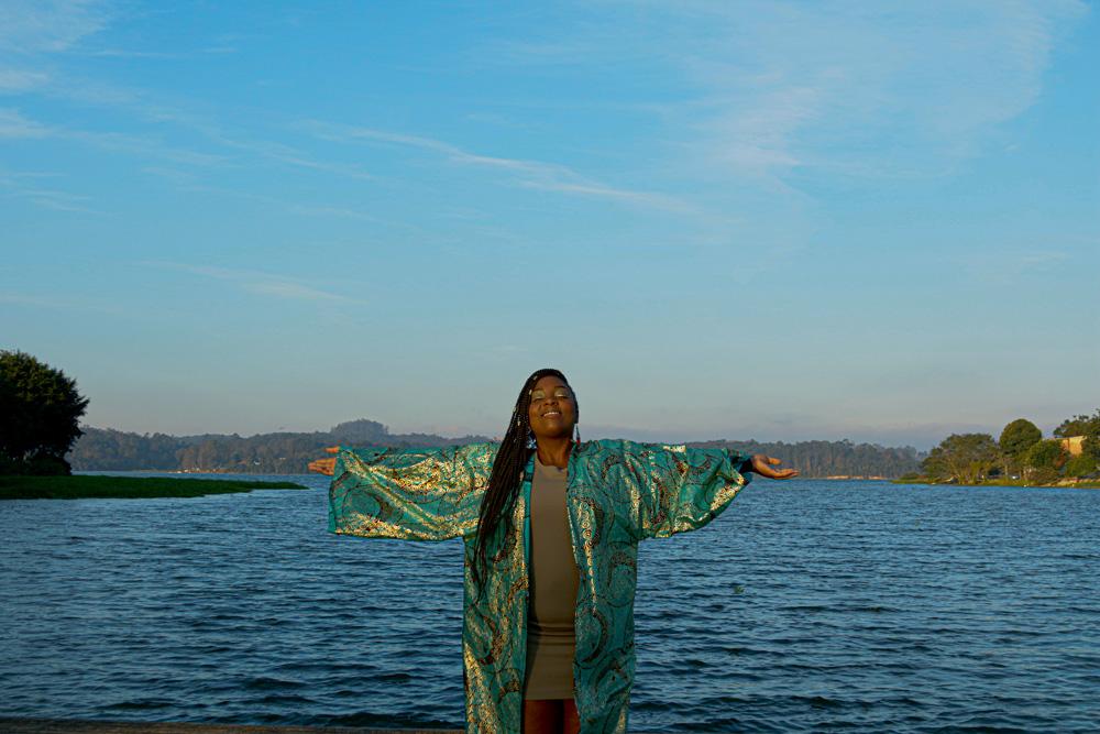 Mulher negra posa com braços abertos em frente a um grande lago