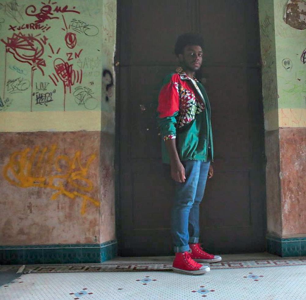 Jovem negro posa em frente a uma porta, em cenário com pinturas de tinta nas paredes