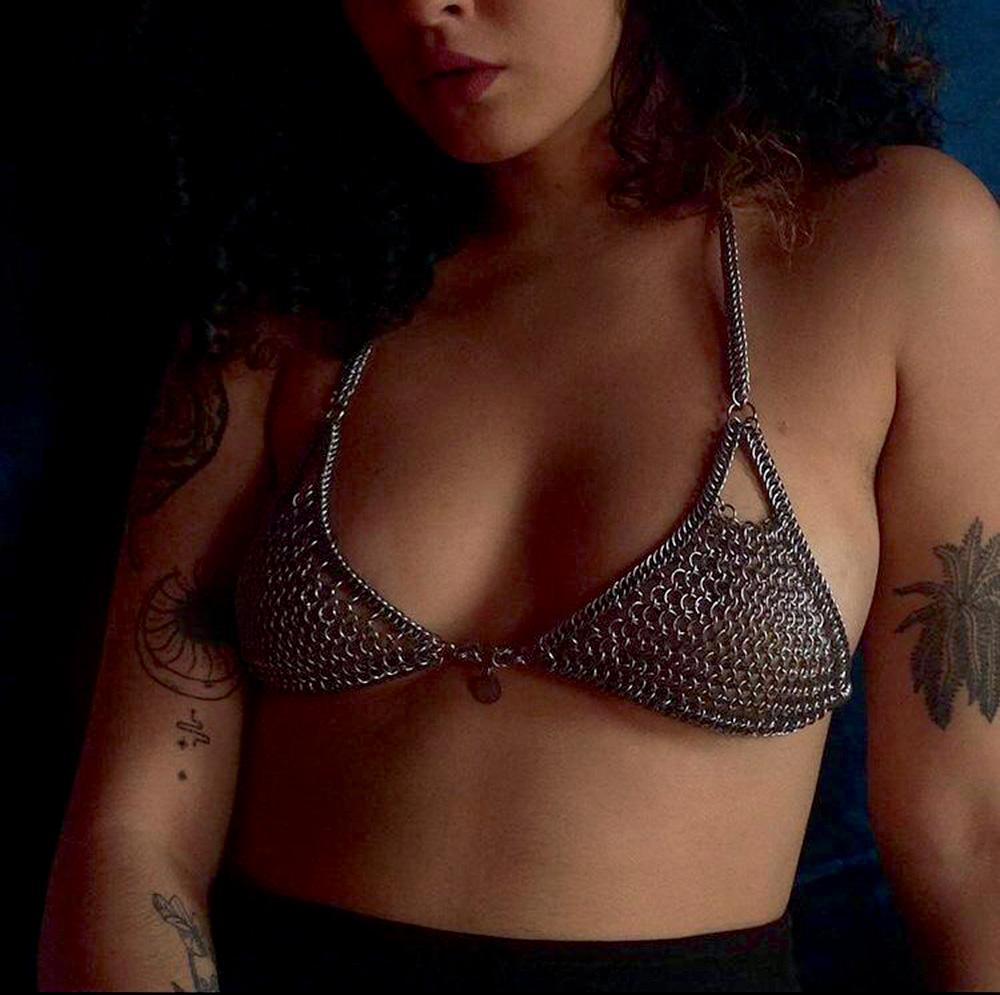 Foto mostra do nariz para baixo de uma mulher até sua cintura. Ela veste um top feito de argolas metálicas