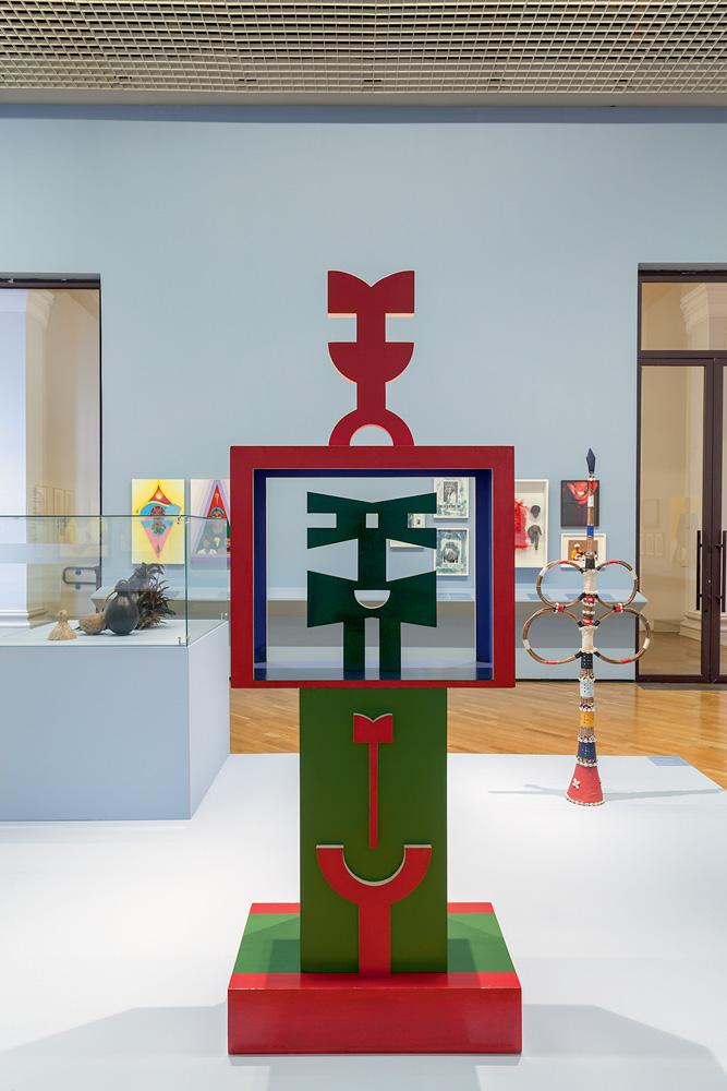 Escultura de Rubem Valentim em uma sala de museu. A obra é verde e vermelha e tem algumas formas geométricas