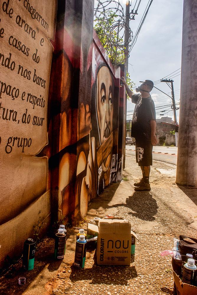 artista atuando sobre um grafite, que ele está restaurando