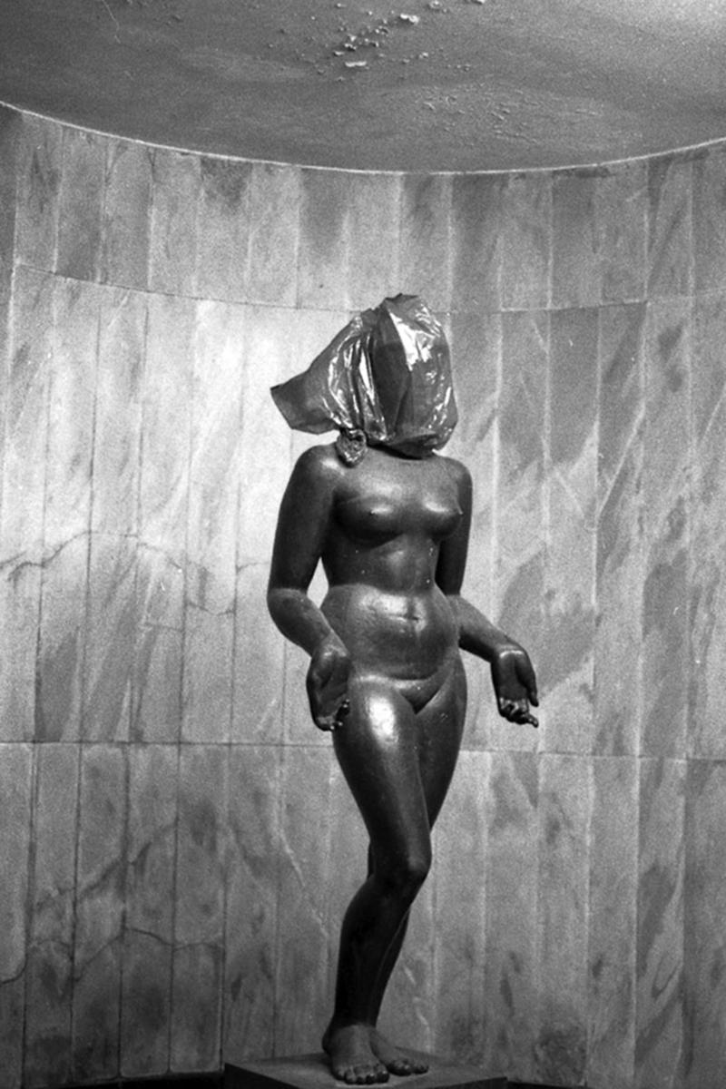 A imagem mostra uma estátua de uma mulher nua com saco em sua cabeça.
