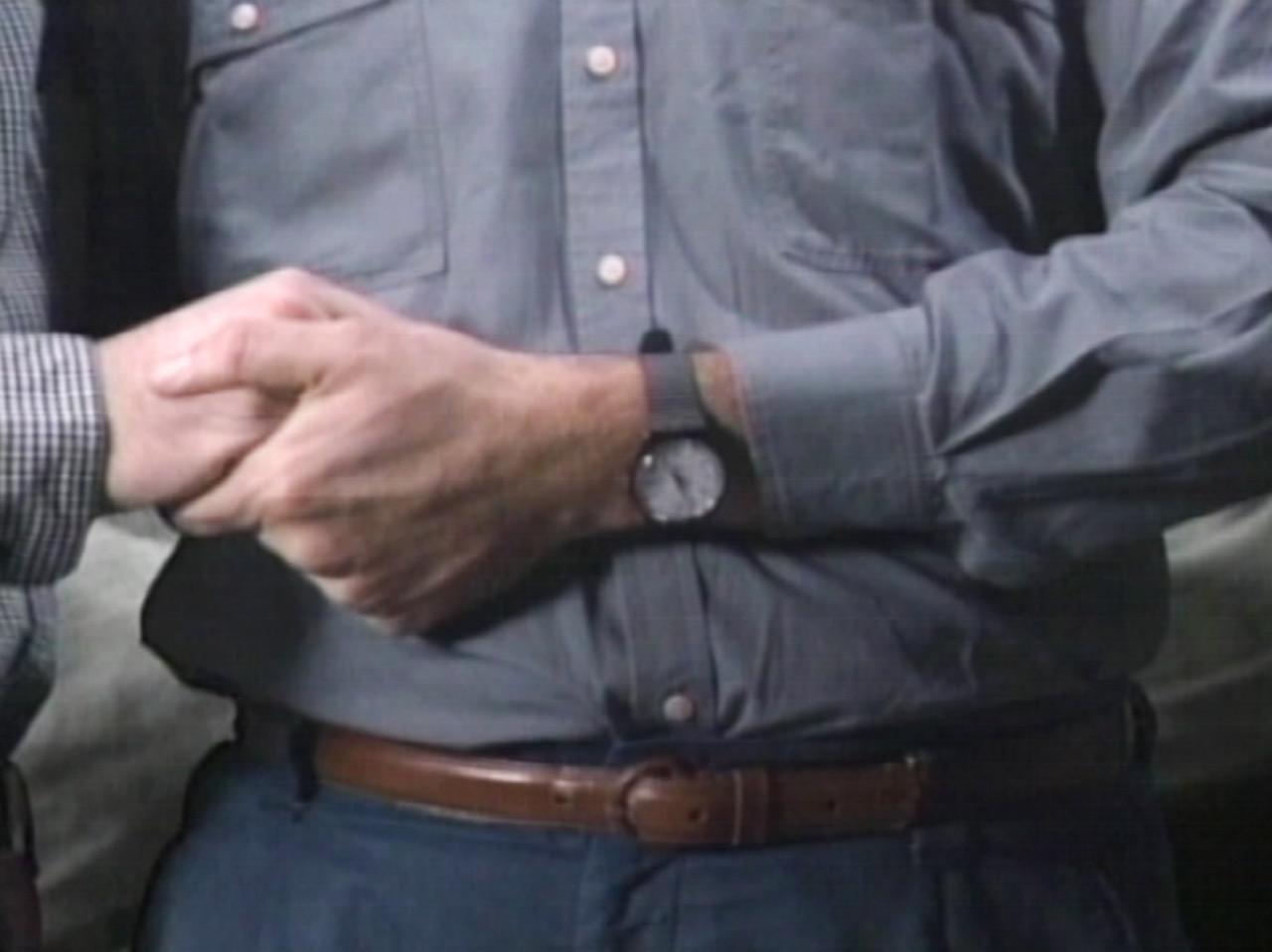 A imagem é uma foto na altura da barriga de um homem. No frame é possível ver a mão dele segurando a mão de outra pessoa com um relógio no seu pulso.