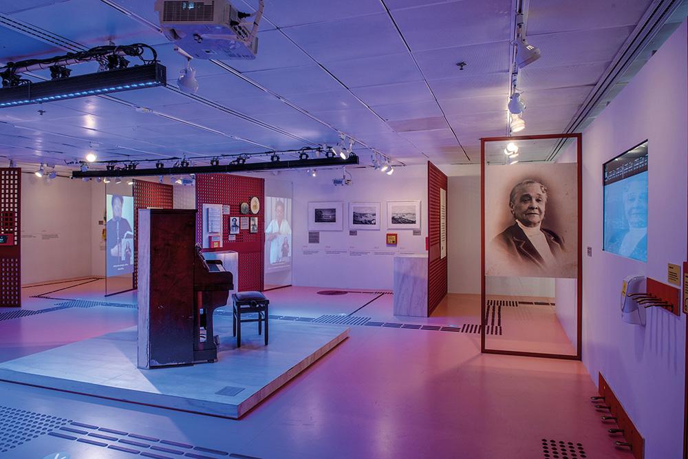Sala no Itaú Cultural. A luz é roxa e há pinturas, telões e gravuras que remetem a Chiquinha Gonzaga